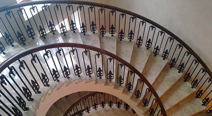 Кованые перила с деревянным поручнем на витой лестнице